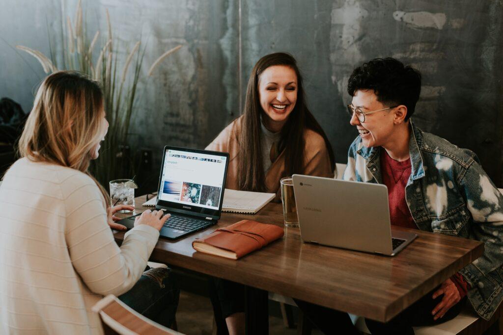 drei Studentinnen sehen sich Webdesign auf ihren Laptops an und lachen