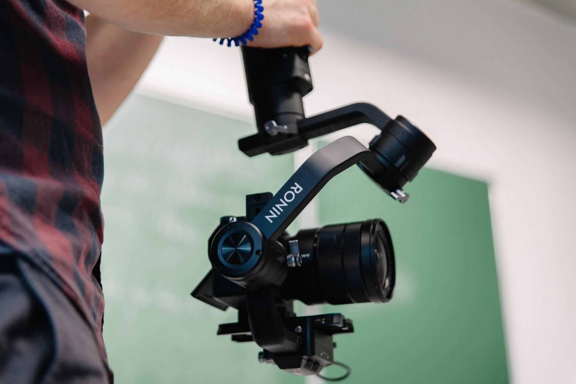 Junge hält Sony Alpha Kamera und Ronin Gimbal in der Hand zum Videodreh