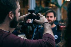 Junger Mann dreht ein Video mithilfe einer Videokamera